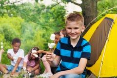 Garçon tenant le bâton avec des guimauves pendant le camping Photo stock