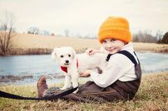 Garçon tenant le chien maltais par l'étang dans le pays Photographie stock