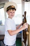 Garçon tenant le volant du bateau Photographie stock libre de droits