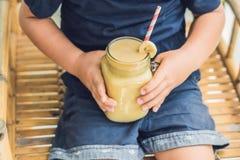 Garçon tenant un smoothie de banane, concept approprié de nutrition photographie stock