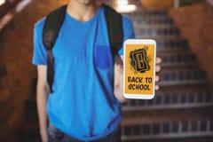 Garçon tenant un téléphone avec de nouveau au texte d'école sur l'écran Photographie stock libre de droits
