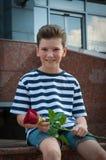 Garçon tenant une rose et un sourire Le concept de l'amour Images libres de droits