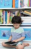 Garçon thaïlandais d'enfant jouant ou lisant le comprimé pour l'étude dans la chambre photo libre de droits