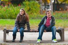 Garçon timide et la fille s'asseyant en stationnement Photographie stock libre de droits