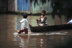 Garçon tirant le canoë avec la fille, Amazone, Brésil photographie stock libre de droits