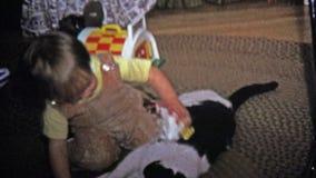 1973 : Garçon tracassant un chat patient avec le nouveau jouet de Noël banque de vidéos
