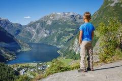 Garçon trimardant à la cascade de sept soeurs dans Geirangerfjord norway image libre de droits
