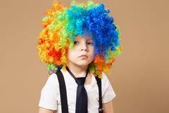 Garçon triste de clown avec la grande perruque colorée Photos stock