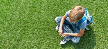 Garçon triste malheureux de renversement seul s'asseyant sur l'herbe photographie stock libre de droits
