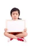 Garçon triste s'asseyant avec le blanc vide dans des mains Photos stock