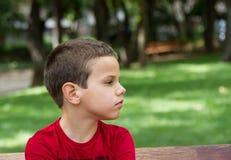 Garçon triste sur un banc de parc Images libres de droits