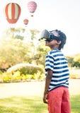 Garçon utilisant le casque de réalité virtuelle de VR avec l'interface Image stock