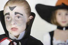 Garçon utilisant le costume de Dracula avec la fille à l'arrière-plan Photo stock
