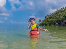 Garçon utilisant un gilet de sauvetage, plongée à l'air en mer photos stock