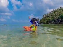 Garçon utilisant un gilet de sauvetage, plongée à l'air en mer à la plage de salade de Haad, KOH Phangan Suratthani photographie stock libre de droits