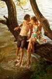 Garçon vilain et fille s'asseyant sur une branche au-dessus de l'eau, riant, ayant parler d'amusement Image stock