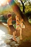Garçon vilain et fille s'asseyant sur une branche au-dessus de l'eau, riant, ayant parler d'amusement Photos stock