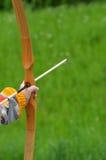 Garçon visant l'arc en bois fait maison dehors Images stock
