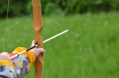 Garçon visant l'arc en bois fait maison dehors Photos libres de droits