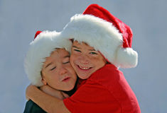 Garçons étreignant avec des chapeaux de Noël en fonction Photo stock