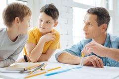 Garçons agréables parlant avec le père tandis qu'il travaillant au modèle Images libres de droits