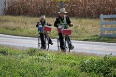 Garçons amish portant des gilets de sécurité et montant des vélos Photos stock