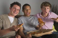 garçons appréciant la pizza d'adolescent Images libres de droits