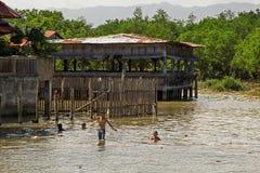 Garçons asiatiques nageant en rivière photos stock
