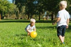 Garçons attentifs jouant avec une boule dehors photos stock