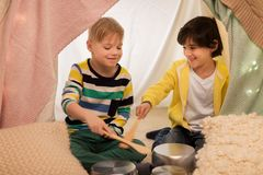Garçons avec des pots jouant la musique dans la tente d'enfants à la maison Images stock