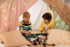 Garçons avec des pots jouant la musique dans la tente d'enfants à la maison Photo stock