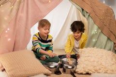 Garçons avec des pots jouant la musique dans la tente d'enfants à la maison Image libre de droits