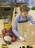 garçons avec des tournevis réparant le tabouret en bois Photos stock