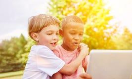 Garçons avec l'ordinateur portable se renseignant sur la technologie Photos stock