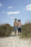 Garçons avec le filet de pêche marchant sur des dunes de sable Photo stock