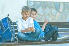 Garçons avec le téléphone portable se reposant sur le banc dehors Images libres de droits