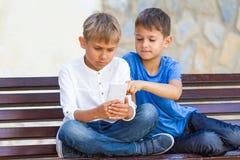 Garçons avec le téléphone portable se reposant sur le banc dehors Photos libres de droits