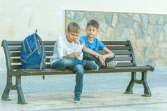 Garçons avec le téléphone portable se reposant sur le banc dehors Photo libre de droits