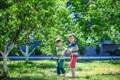 Garçons ayant l'amusement avec le jardin de arrosage de fruit dans le village dehors Photos libres de droits