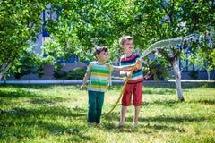 Garçons ayant l'amusement avec le jardin de arrosage de fruit dans le village dehors Photos stock