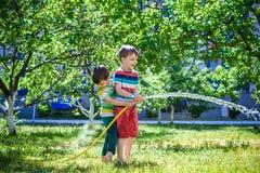 Garçons ayant l'amusement avec le jardin de arrosage de fruit dans le village dehors Images stock
