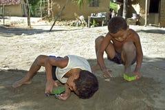 Garçons brésiliens jouant à la maison avec des camions de jouet Photographie stock