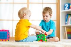 Garçons d'élève du cours préparatoire d'enfant en bas âge d'enfants jouant le jouet logique apprenant des formes et des couleurs  image libre de droits