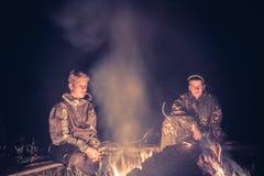 Garçons d'adolescents dans le camp par le feu pendant la nuit Photos libres de droits