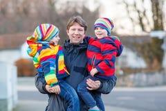 Garçons d'enfant de participation de père, fils sur le bras dehors Image stock