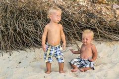 Garçons d'enfant en bas âge s'asseyant sur la plage photos stock