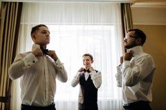 Garçons d'honneur élégants aidant le marié heureux étant prêt dans le morni photographie stock libre de droits
