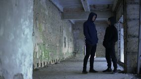 Garçons dans le hoodie parlant dans le bâtiment ruiné, bande adolescente, jeunes criminels banque de vidéos