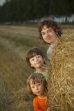 3 garçons dans une meule de foin dans le domaine Image stock