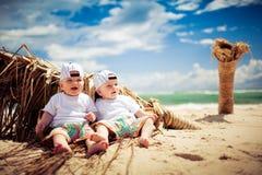 Garçons de jumeau identique détendant sur une plage photographie stock